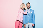 attractive woman telling secret to smiling man on pink and blue background