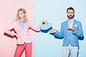 sad woman holding gift and shocked man pointing with hands on pink and blue background