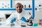 smiling african american biologist holding glasses and looking at camera