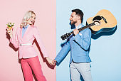smiling woman with bouquet and handsome man with acoustic guitar holding hands on pink and blue background