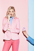 cropped view of man doing marriage proposal to shocked woman on pink and blue background