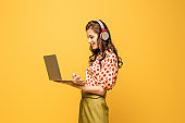 cheerful young woman in wireless headphones using laptop isolated on yellow