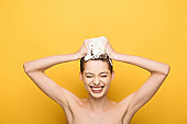 cheerful girl smiling with closed eyes while washing hair on yellow background