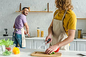 selective focus of happy homosexual man looking at curly partner while washing plate