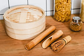 selective focus of bamboo steamer near cooking utensils and jars with dried pasta