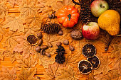 top view of autumnal decoration and food scattered from wicker basket on golden foliage on wooden background