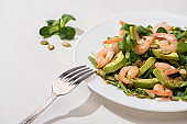 selective focus of fresh green salad with shrimps and avocado on plate near fork on white background