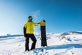sportsman in helmet holding snowboard while standing on white snow
