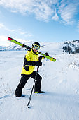 skier in helmet and goggles walking with sticks on white snow in mountains