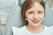 Happy girl with orthodontic braces in professional clinic