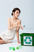 brunette woman in silk dress throwing plastic bottle in trash bin with recycle sign on white, ecology concept