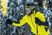 skier in helmet holding ski sticks in winter