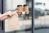 Cropped view of waitress holding paper bag and coffee to go near cafe on urban street