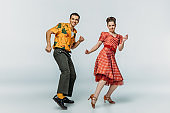 cheerful dancers looking at camera while dancing boogie-woogie on grey background