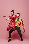 stylish dancer holding woman while dancing boogie-woogie on pink background