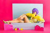 sexy pop art girl in purple wig as doll blowing bubble gum while sitting in blue box with balls and shopping bags, on pink