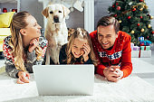 happy family laughing while watching movie on laptop near dog on christmas