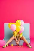 young woman as doll holding balloons and sitting in blue box with balls and shopping bags, on pink