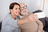 happy woman and senior man taking selfie on mobile phone on blurred foreground