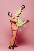 stylish dancer holding girl while dancing boogie-woogie on pink background