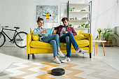 man using smartphone and woman reading book while robotic vacuum cleaner washing carpet in living room