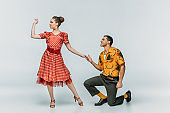 handsome man standing on knee and inviting pretty woman to dance boogie-woogie on grey background