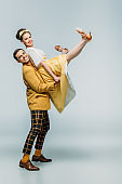 stylish dancer holding happy girl while dancing boogie-woogie on grey background