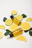 juicy lemon and lime slices near bottles with citrus essential oil and rose leaves on white
