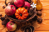 wicker basket with autumnal harvest on wooden background