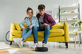 man and young woman looking at robotic vacuum cleaner washing carpet in living room