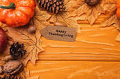 top view of pumpkin, autumnal decoration and happy thanksgiving card on wooden background