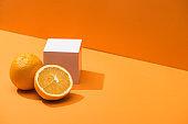 fresh oranges and white cube on orange background