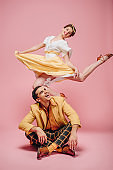 cheerful man sitting on floor and happy girl jumping while dancing boogie-woogie on pink background
