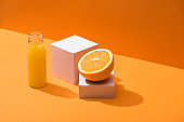 fresh juice in glass bottle near orange half and white cubes on orange background