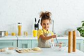 cheerful african american kid holding whisk near raw dumplings on cutting board