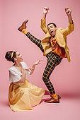 cheerful girl sitting on floor and excited man raising leg while dancing boogie-woogie on pink background