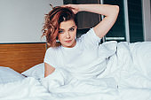 beautiful girl lying in bed in morning during self isolation