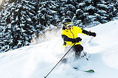 sunshine on skier in goggles and helmet holding ski sticks while skiing near firs
