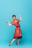 beautiful dancer looking at camera while dancing boogie-woogie on blue background