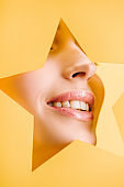 cropped view of beautiful woman with shiny lips in paper star shaped hole smiling isolated on yellow