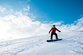 athletic snowboarder in helmet riding on slope against blue sky with clouds