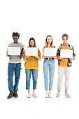 Smiling multiethnic teenagers with backpacks holding laptops on white background