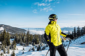 happy skier in goggles holding ski sticks against blue sky in mountains