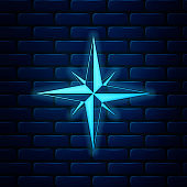 Glowing neon Wind rose icon isolated on brick wall background. Compass icon for travel. Navigation design. Vector Illustration