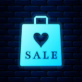 Glowing neon Shoping bag with an inscription Sale icon isolated on brick wall background. Handbag sign. Woman bag icon. Female handbag sign. Vector Illustration