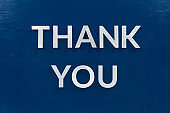 the words thank you laid with aluminium white metal letters on painted flat blue background - directly above in flat lay composition