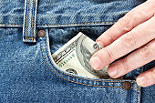hand takes US dollar banknote from the right front pocket of blue jeans. Concept of saving money or pocket expenses