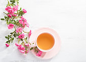 Cup of tea and branch of small pink  roses on  white rustic table. Top view.
