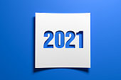 A piece of curved memo paper with the cut out number 2021 on blue background. Concept for events in the year 2021 and New Year 2021.