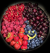 Variety of berries and drawn smile